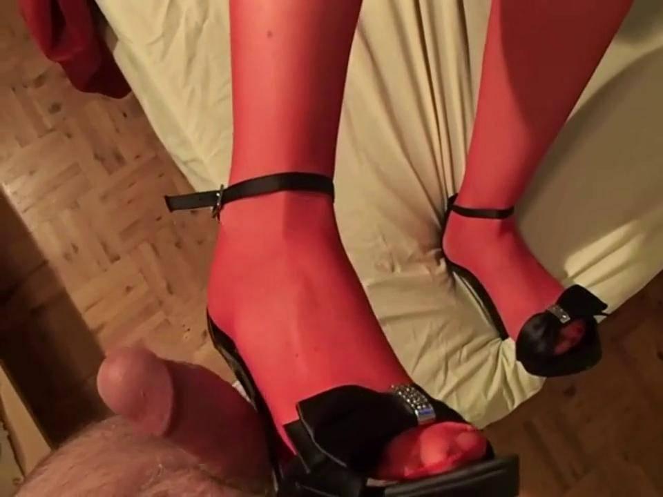 Сучка в красных чулках дрочет член ножками