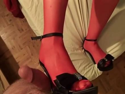 Шалунья в черных туфлях и красных капронках ножкой теребит хуй пикапера