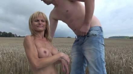 Опытная дамочка с большими сиськами берет в рот длинный стержень мужика посреди поля