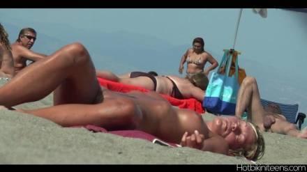 Обнаженные загорелые барышни ласкают свои тела на нудистском пляже и немного шалят