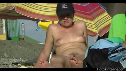 На нудистском пляже парочки и некоторые одиночки шалят сосвоими прелестями с достоинствами пртнера